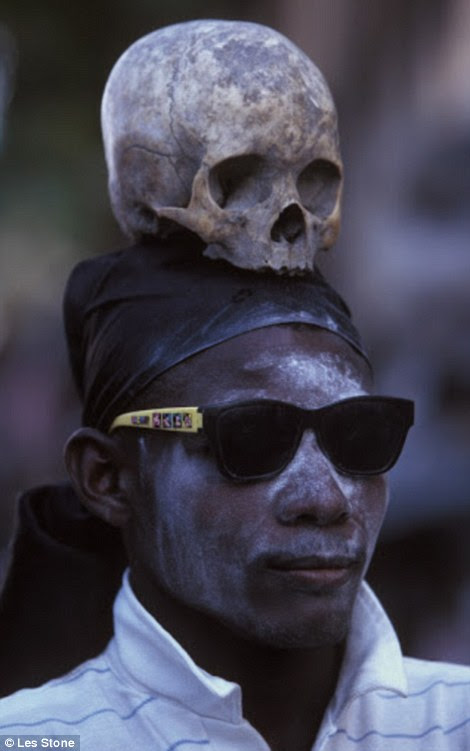 On a street in Port au Prince, during the Day of the Dead a man walks among the crowds with a scull on his head