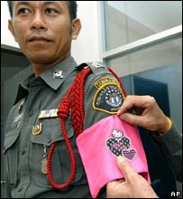"""A police officer wears a pink armband featuring 'Hello Kitty"""" to show reporters"""