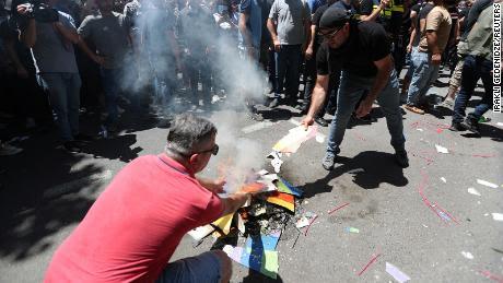 Los manifestantes anti-LGBT queman una pancarta de arcoíris mientras participan en una manifestación antes de la marcha del lunes.