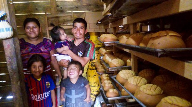 Diego Matom, a member of the Ixil indigenous community, poses happily with his family, surrounded by fresh loaves of bread which were baked thanks to community electricity generation, which has given his business a big boost, in the 31 de Mayo village in the mountainous ecoregion of Zona Reina, in northwestern Guatemala. Credit: Edgardo Ayala/IPS