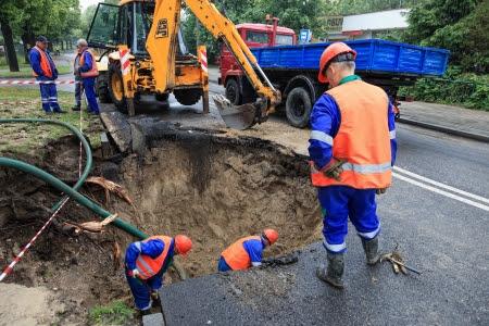 Gdansk, Polonia - 22 de junio trabajadores que reparan la carretera dañada - Las consecuencias de la ruptura de la línea 22 de junio 2012 en Gdansk, Polonia Foto de archivo - 14223892