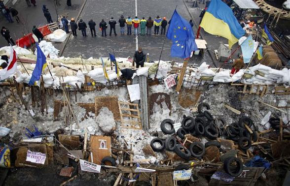 Pro-European integration demonstrators stand guard near a barricade during a rally at Independence Square in Kiev in this December 17, 2013 file photo. REUTERS-Marko Djurica-Files