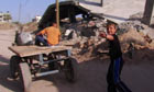 Children run through a rubble-strewn area of Gaza