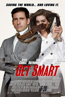 Maxwell Smart, wearing suit and holding a gun, his tie blown to the side, covering the face of Agent 99 who is standing behind him wearing a a white jacket.