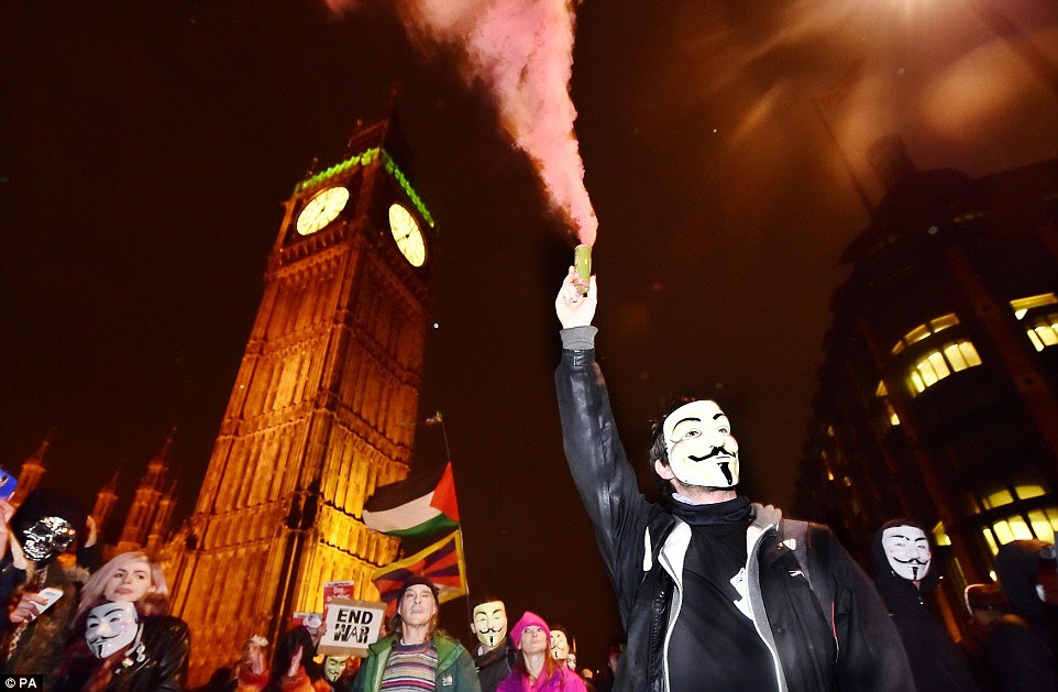 A masked protester carries a smoke bomb above the crowd as the march makes its way from Trafalgar Square towards Whitehall