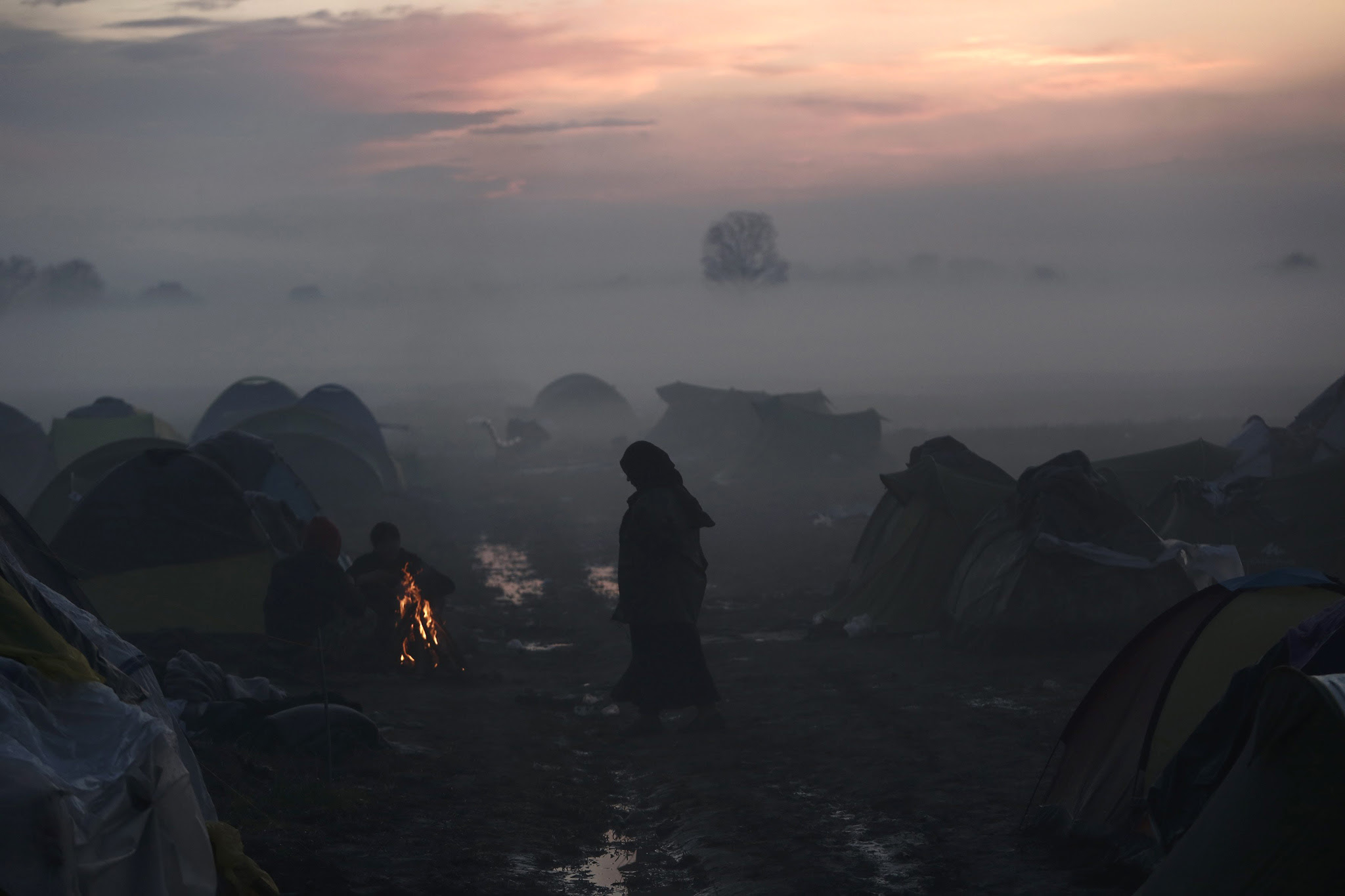 Still thousands of refugees massing in Idomeni to enter Macedonia...epa05205764 Refugees try to warm themselves with a fire at a refugee camp during a foggy day at the border between Greece and the Former Yugoslav Republic of Macedonia (FYROM), near Idomeni, northern Greece, 11 March 2016. Greece has registered in its territory some 36,000 migrants trapped due to entry restrictions already imposed by Macedonia in recent months, by denying entry to all those who are considered economic migrants, prohibiting the passage of Afghans, and finally denying entry to all Syrians and Iraqis who are not from combat areas.  EPA/YANNIS KOLESIDIS