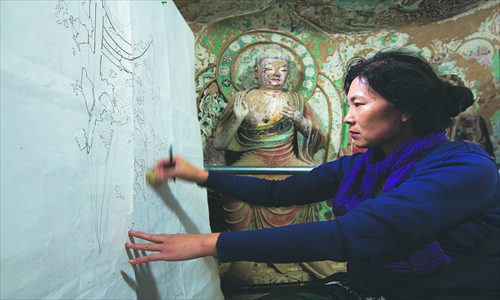 Guan Jinwen, who went to the institute in 1983, works on her copy in a cave of the Mogao Grottoes. Photo: CFP