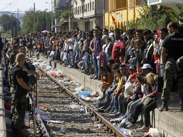 Migrantes esperam trem que os levará à Sérvia neste domingo (23) em estação de Gevgelija, na Macedônia (Foto: AP Photo/Boris Grdanoski)