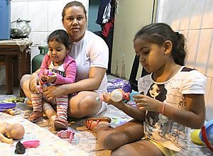 Monique da Silva brinca com sua filha, no colo, e com criança de uma vizinha no Jardim Ãngela