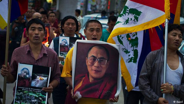 Tibetan exiles carry Tibetan flags and a portrait of the spiritual leader Dalai Lama, center, during a candlelit vigil in Dharmsala, India, Tuesday, July 17, 2012 to express solidarity with Lobsang Lozin, an 18-year-old Tibetan monk whom they say died of self-immolation in southwestern China's Sichuan province. The International Campaign for Tibet says 42 Tibetans have self-immolated since March 2011. Activists say the self-immolations are in protest of Beijing's heavy-handed rule in the region. The Chinese government has confirmed some but not all of the deaths by self-immolation. (AP Photo/ Ashwini Bhatia)