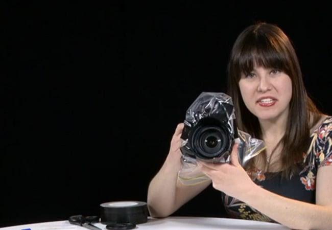 Chica con una cámara cubierta con una bolsa para cubrirla de la lluvia