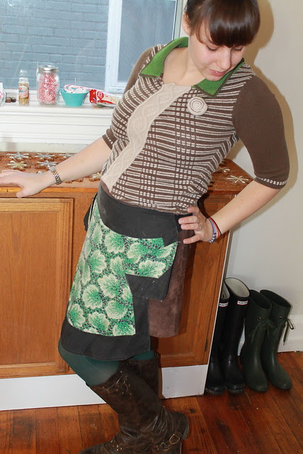 Christmas eve outfit: green tights, leather boots, vintage suede mini skirt, Anthopologie sweater, vintage apron