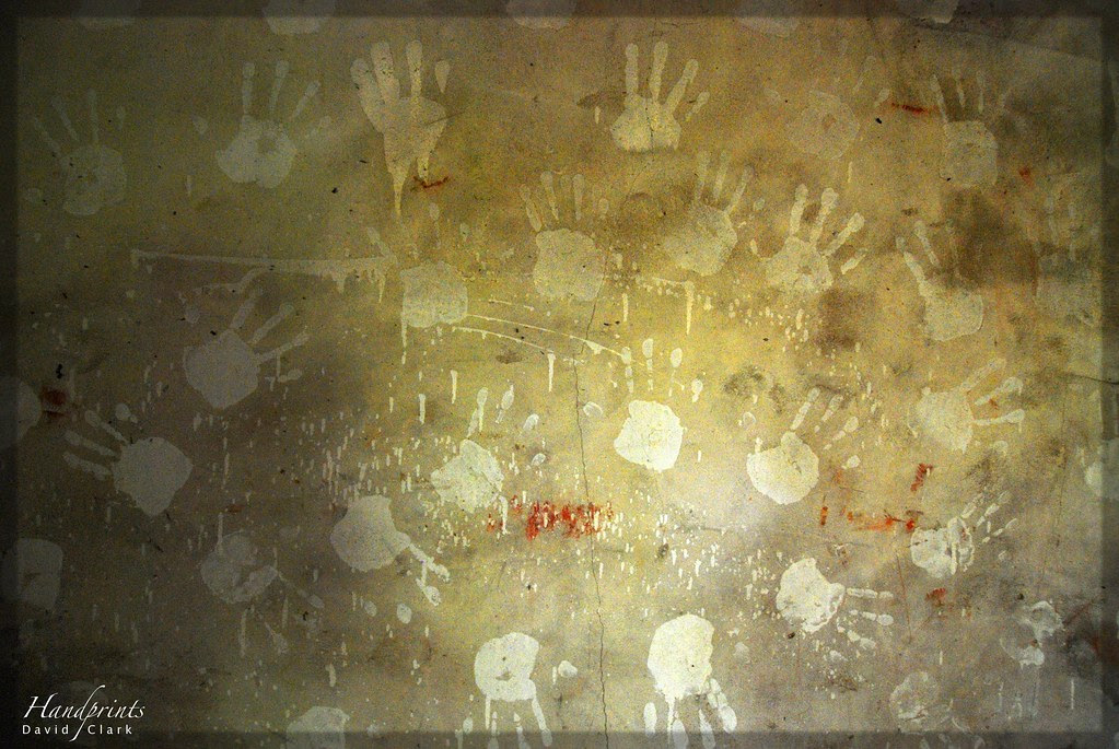 Handprints made in paint on a decaying wall.