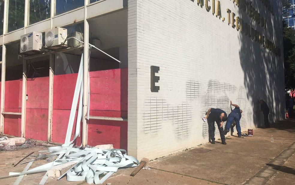 Funcionários limpam pichações na fachada do Ministério da Ciência e Tecnologia após manifestação contra governo Temer (Foto: Luiza Garonce/G1)
