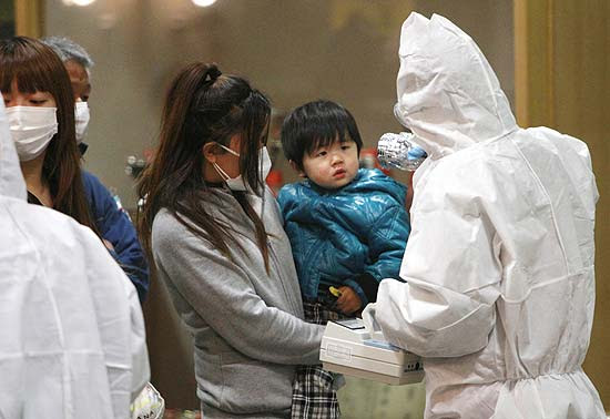Criança é testada para atestar exposição à radiação em Koriyama, na região de Fukushima; brasileiros são retirados