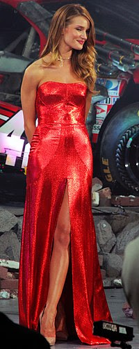 A blonde woman wearing a red dress and a gold necklace. Stones and a car can be seen behind her.