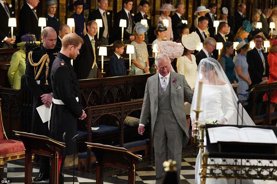 El Príncipe Harry observa mientras su padre, el Príncipe Carlos, acompaña a Meghan Markle por el pasillo de la Capilla de San Jorge