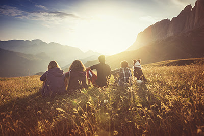 Group of people in a field watching the sun set behind mountains