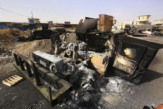 Burnt vehicles belonging to Iraqi security forces are pictured at a checkpoint in east Mosul, one day after radical Sunni Muslim insurgents seized control of the city, June 11, 2014.  REUTERS-Stringer