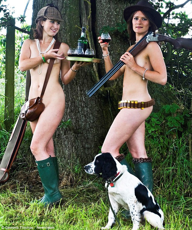 In one of the photos two women carrying a tray and glasses of port stand completely naked in a wooded area - with their modesty only covered by bag straps and shotguns