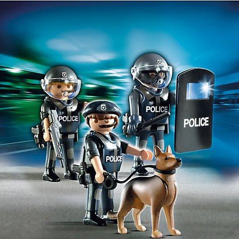 """Série """"Ação da Cidade"""" do Playmobil tem policiais da tropa de choque, com escudos e máscaras de gás segurando armas grandes, clubes e cachorros pronto para morder a cara fora de manifestantes.  Tudo parte da agenda de normalizar, um estado policial opressor violento."""