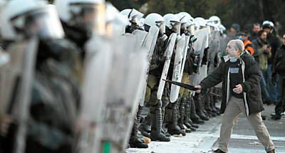 Homem protesta com guarda-chuva em frente a barreira policial em Atenas