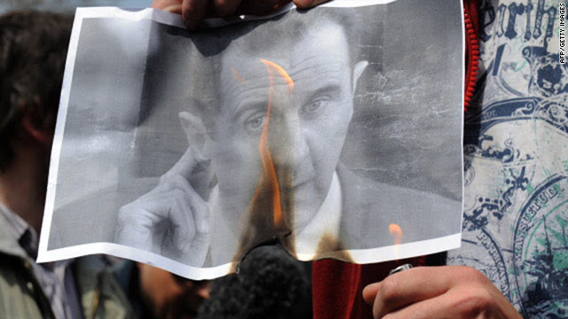 A Syrian opposition protester burns an image of President Bashar al-Assad.