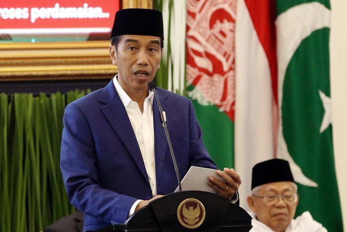 Indonesian President Joko Widodo stands at a lectern talking into a microphone.