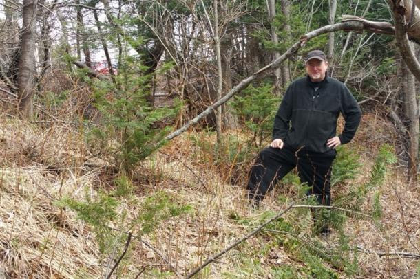 Wayne MacIsaac stands near what he believes may be the remnants of a Norse fortification wall.