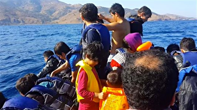 Des migrants traversent la mer Égée sur un bâteau pneumatique.