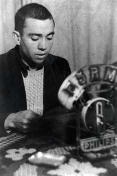 Fotografía de Miguel Hernández leyendo frente a un micrófono