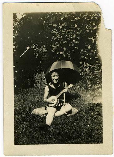Snapshot: Backyard Woman With Umbrella And Banjo