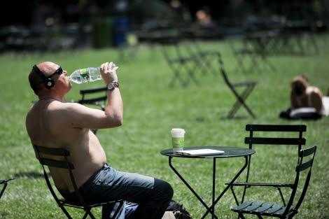 Un hombre bebe agua en un parque de Nueva York. | Afp