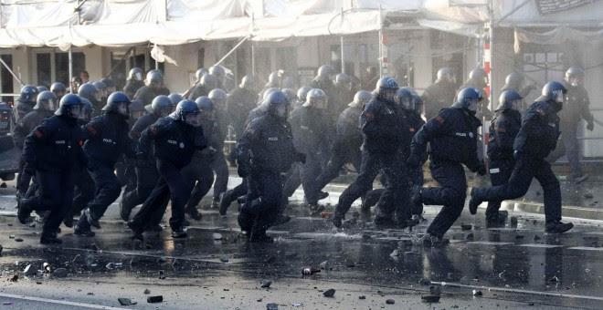 Un grupo de policías antidisturbios corren hacia manifestantes en Hamburgo. /REUTERS