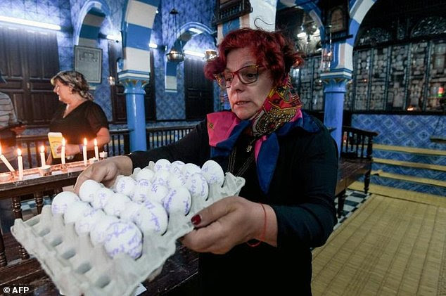 A French Jewish woman carries a carton of eggs with her family's wishes written on them at the Ghriba synagogue on the Tunisian island of Djerba on May 14, 2017