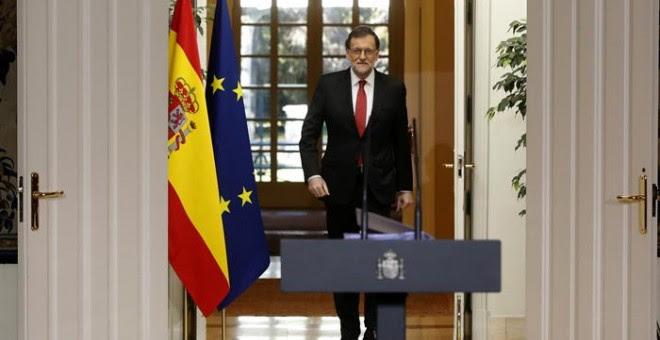 El presidente del Gobierno, Mariano Rajoy, se dirige a la sala del Palacio de la Moncloa. /EFE