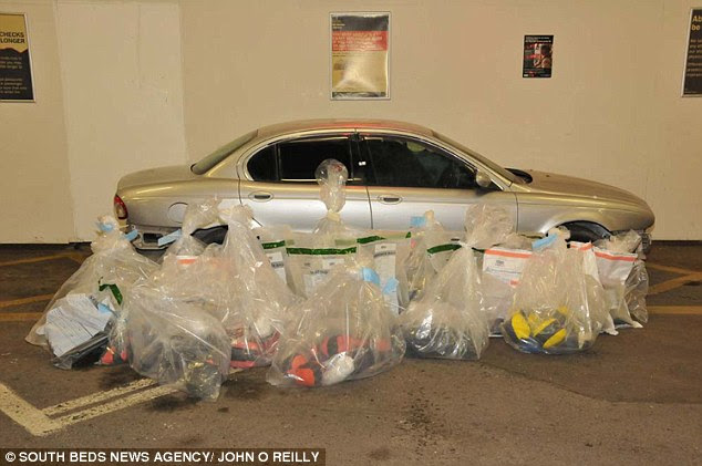 Haul: Heroin with a £37million street value was smuggled into Britain in the bumpers, dashboard and engine of a battered Jaguar X-Type, a court heard. Here is a photograph of the car with the colour-coded bags of heroin