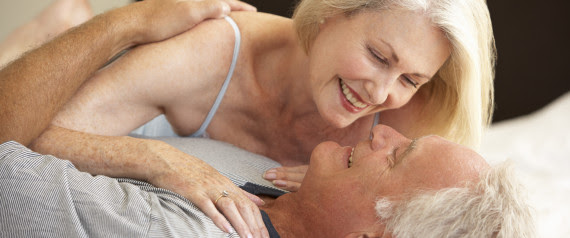 older couple kissing in bed