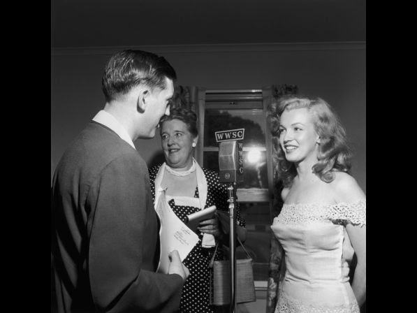 Monroe stands at a WWSC microphone in 1949 with a man and woman during a 'Photoplay Magazine' contest event, Williamsburg, New York. Monroe was in New York City to promote her new film, 'Love Happy' and traveled to Williamsburg to present the contest winner with the key to a new house.