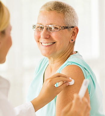 A doctor giving a flu shot to a female patient