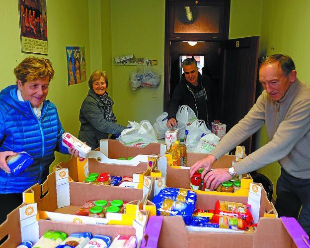 Los voluntarios de Cáritas del Juncal, ayer, ordenando los alimentos donados./F. DE LA HERA