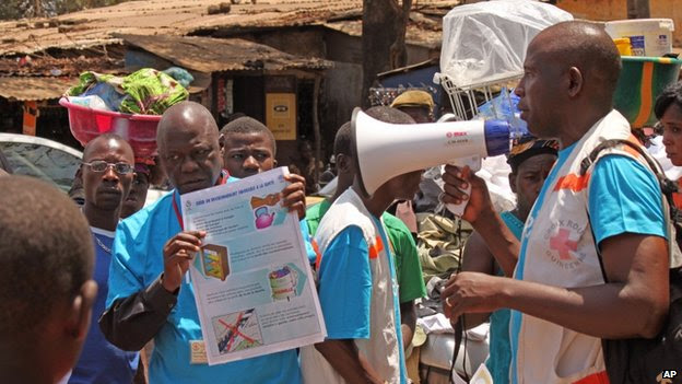 Health workers teach people about the Ebola virus and how to prevent infection, in Conakry, Guinea - 31 March  2014