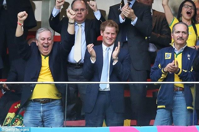 Hooray!  Príncipe Harry (centro) e Brasil Ministro do Esporte Aldo Rebelo (à direita) comemora o primeiro gol de Neymar para o Brasil durante a partida da Copa do Mundo contra Camarões, em Brasília