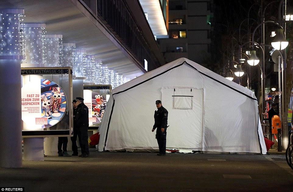 A polícia do lado de fora de uma tenda perto do mercado de Natal em Berlim como os feridos no acidente devastador são tratados