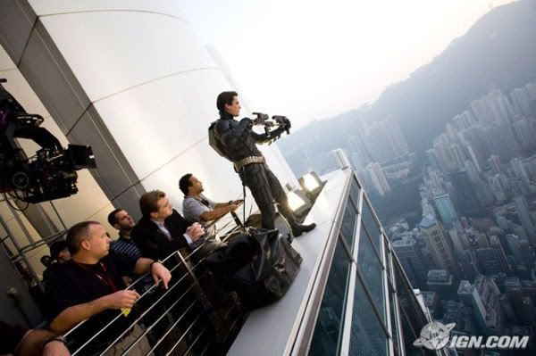 Director Christopher Nolan and his crew look on as Christian Bale rehearses a scene for THE DARK KNIGHT on a skyscraper overlooking Hong Kong.