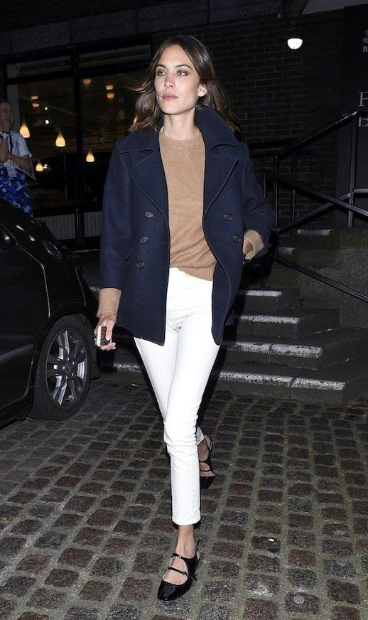 Le Fashion Blog Alexa Chung Street Style Navy Coat Camel Sweater White Jeans Black Strappy Buckled Flats Via Popsugar