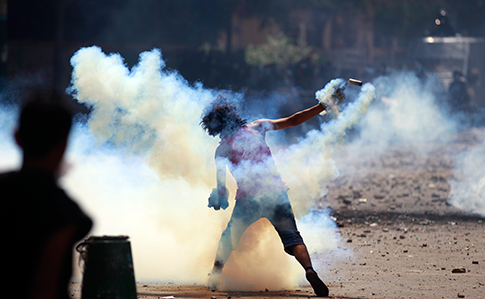 An Egyptian protester throws a tear gas canister toward riot police during clashes near the U.S. Embassy in Cairo, Egypt, Sept. 13, 2012. (AP)