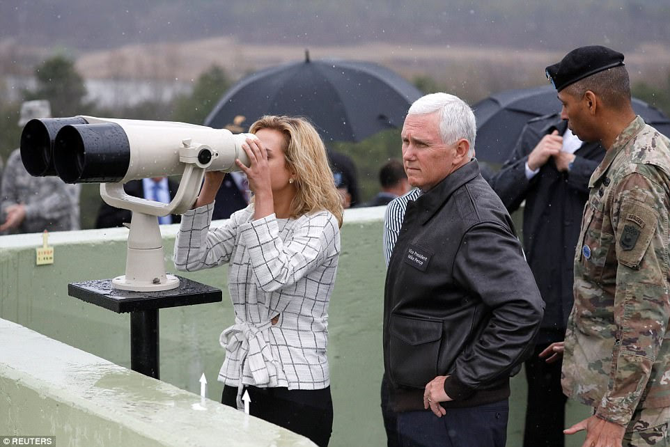 Pence stands next to his daughter, Audrey, as she peers out over the DMZ through a pair of binoculars inside an observation post