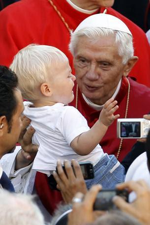 Un Bambino piange al cospetto di papa Benedetto XVI, il Che ha celebrato la Messa dell'Assunzione NELLA residenza estiva di Castel Gandolfo (Reuters)
