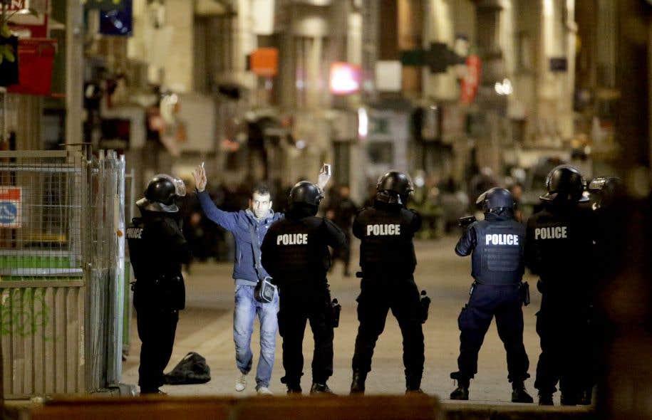Un passant lève les bras devant l'escouade tactique postée devant l'appartement de Saint-Denis, dans la nuit de mardi.